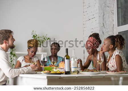 Multiracial Group Of Young Friends Enjoying Meal at Home - stock photo