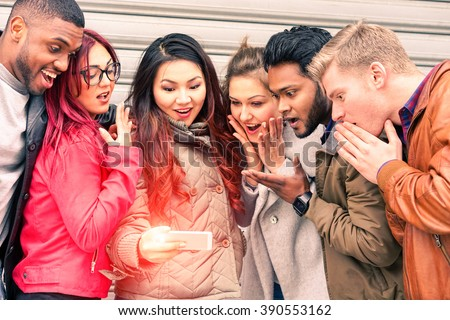 Multiracial group of young friends surprised face looking mobile phone new miracles technology - Mixed race best friendship and astonished facial expression concept - Main focus Indian man at right  - stock photo
