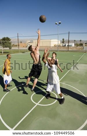 Multiracial group playing basket ball on court - stock photo