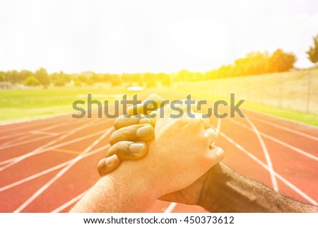 Multiracial runners shaking hands before athletic competition with back lighting - Multi-ethnic people showing respect against racism - Fair competition concept - Soft warm filter - stock photo