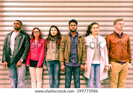 Multiracial serious people lineup as mugshot is standing next to metal rolling shutter - Unemployed multi ethnic friends line up outdoor - Concept of discrimination and youth concern for the future - stock photo