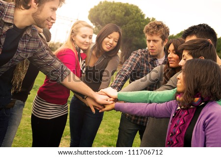 Multiracial Students with Hands on Stack, Italy - stock photo