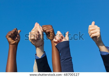 Multiracial Thumbs Up Against Blue Sky - stock photo