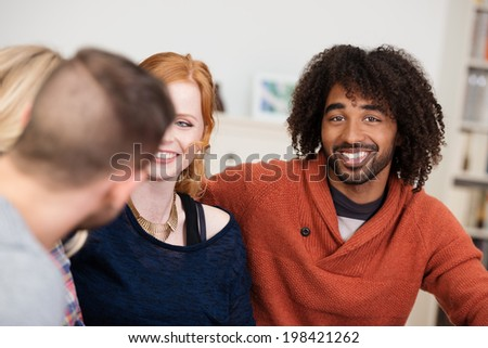 Multiracial young group of friends sitting relaxing at home with focus to a handsome young African American man with a friendly smile and curly afro hairdo - stock photo