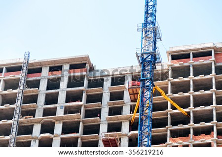Multistoried building construction with tower crane.