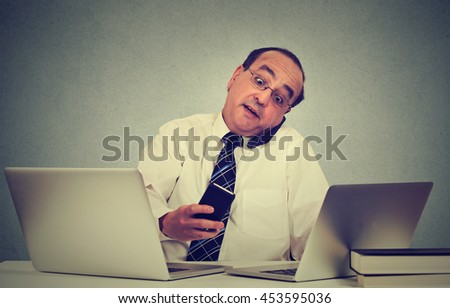 Multitasking middle aged business man working at his office desk isolated on gray wall background. Busy life of company manager corporate executive. Many errands concept - stock photo