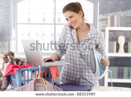 Multitasking woman at home, doing housework, ironing laundry and using laptop computer, talking on mobile phone, smiling.? - stock photo