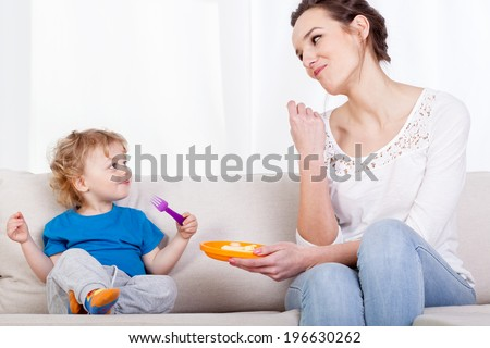 Mum and child eating meal together, horizontal - stock photo