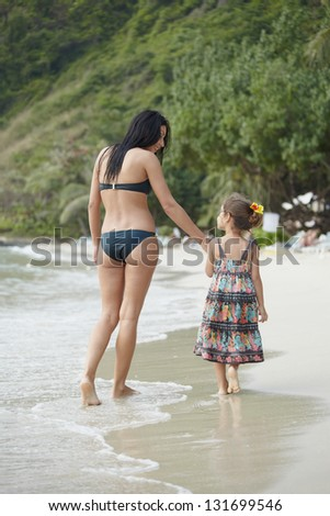 Mum and daughter walking on sea coast