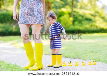 Mum and her little cute kid daughter in yellow rainboots, family look, playing with duck toys in summer park. Active leisure with kids. - stock photo