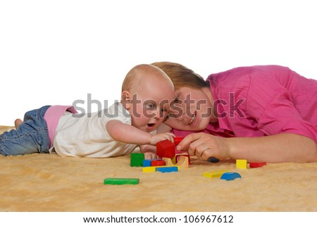 Mum and her small baby lying close together on the floor playing with building blocks as she teaches it coordination and shapes - stock photo
