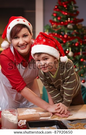 Mum and son having fun at christmas baking, looking at camera, smiling.? - stock photo