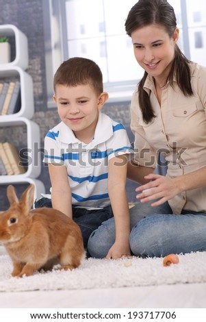 Mum and son having fun with pet rabbit at home, playing on living room carpet.