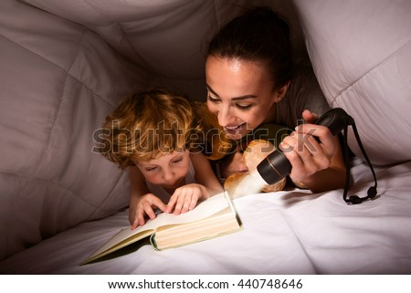 Mum and son reading exciting story - stock photo