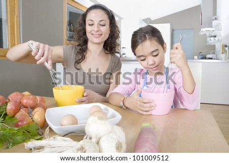 Mum and young daughter beating eggs in a home kitchen. - stock photo