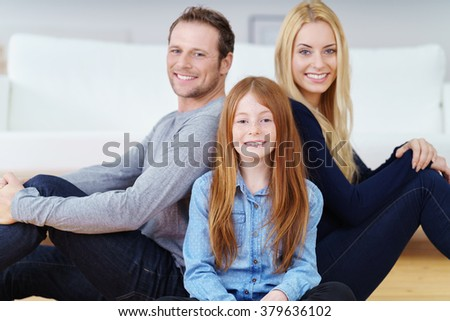 Mum, Dad and their cute little daughter posing sitting back to back on the living room floor smiling at the camera