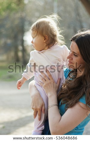 Mum holds the small daughter on hands in park