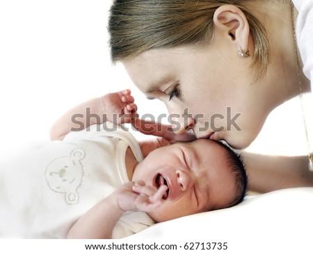 Mum kissing crying baby - stock photo