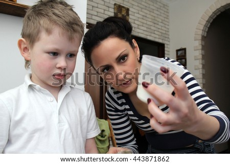 Mum learns to cook his little son. Family concept. Woman holding a measuring cup flour