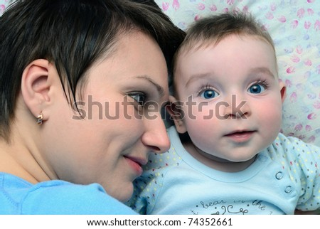 Mum lies near to the child. Looks at it and smiles - stock photo