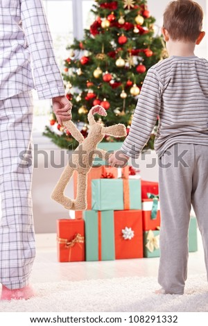 Mum, little son and toy bunny on christmas morning, going to unwrap gift parcel. - stock photo