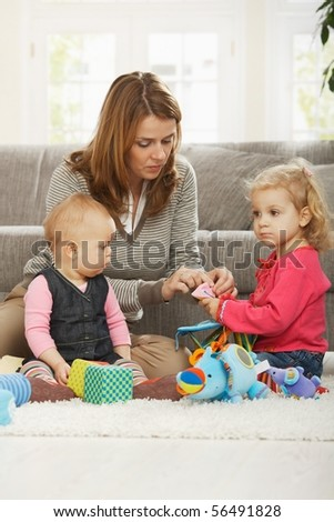 Mum playing on floor with two baby daughters at home.
