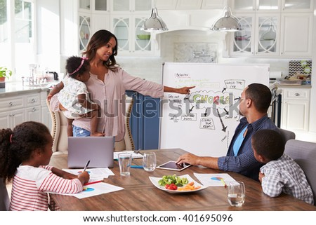 Mum presenting domestic meeting to her family in the kitchen - stock photo
