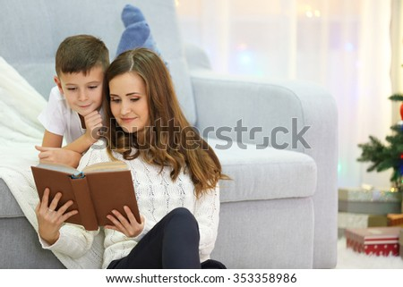 Mum reading book to son in Christmas living room - stock photo