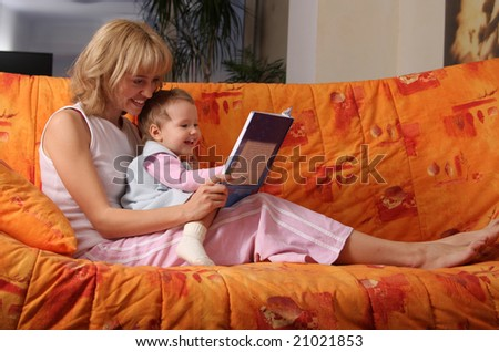 Mum reads the book to a daughter - stock photo