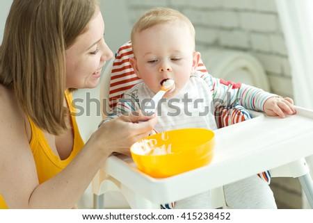 Mum spoon-feeds the child - stock photo