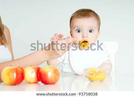 Mum spoon-feeds the child - stock photo