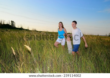 Mum, the daddy and the boy in an autumn field - stock photo