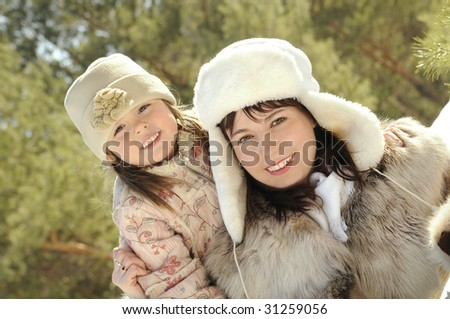 Mum together with the daughter embrace in the winter on the nature