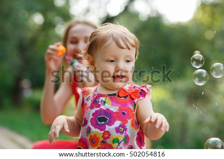 Mum with daughter blowing soap bubbles in park