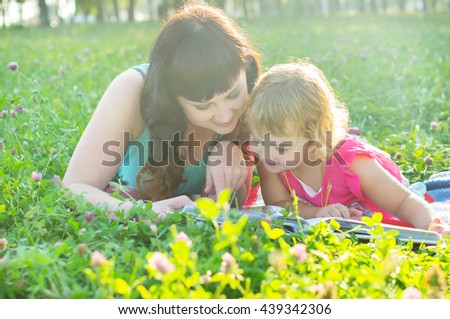Mum with the child lying on the grass - stock photo