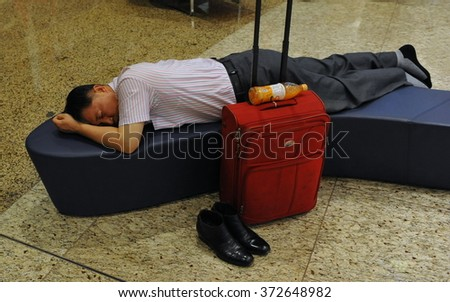 MUMBAI, INDIA - APR 14, 2014: An air traveller rests in the transit lounge at the new terminal T2 of Chhatrapati Shivaji International Airport. The airport first opened in 1942. - stock photo