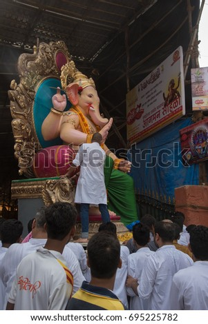 Mumbai, India - August 28, 2016 : Devotees bringing Lord Ganesha from workshop for procession during Hindu Lord Ganesha chaturathi festival along the street at night