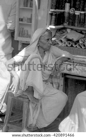 MUMBAI, INDIA - FEBRUARY 15, 1984: lady selling necklaces in the biggest open air city market. The place is everyday populated by thousands of people. - stock photo