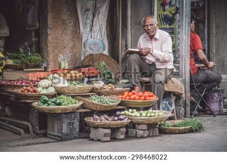 MUMBAI, INDIA - 17 JANUARY 2015: Elderly Indian man writes in book and waits for customer next to grocery shop in market street. Post-processed with grain, texture and colour effect. - stock photo