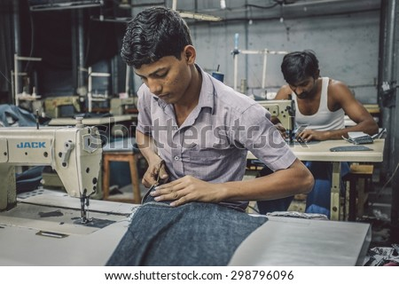 MUMBAI, INDIA - 12 JANUARY 2015: Indian workers sew in clothing factory in Dharavi slum. Post-processed with grain, texture and colour effect. - stock photo
