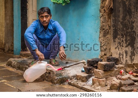 MUMBAI, INDIA - 12 JANUARY 2015: Young Indian man sits and fills water tank in street. Dharavi slum mostly has drinkable tape water in street but not in homes.