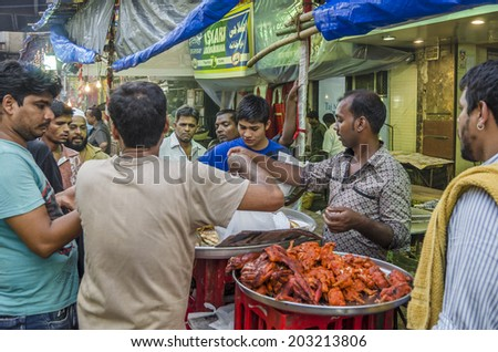 Mumbai, India - July 3, 2014 -  People shopping for food from stall at at crowded Mohammad Ali Road in the evening during Ramzan fasting month - stock photo