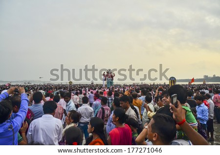 Mumbai, India - September 17, 2013 - Devotee bringing Hindu God Ganesha into the ocean during Ganesha Festival