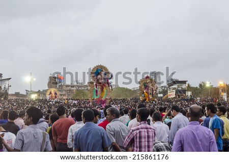 Mumbai, India - September 8, 2014 - Devotees watching, praying and carrying Ganesha idol to be immersed in the sea at Girgaum Chowpatty during Ganesha Festival