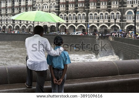 MUMBAI, MAHARASHTRA / INDIA - JUN 11, 2008 : A FATHER AND CHILD ARE LOOKING AT THE TAJ HOTEL DURING THE MONSOON IN INDIA. - stock photo