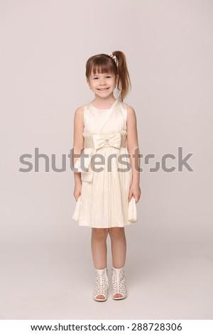 Mummy's little girl happy smiling. Girl in white dress posing in full length. - stock photo