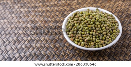 Mung beans in white bowl on wicker background
