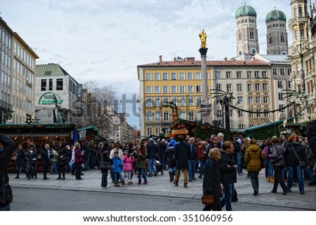 MUNICH, BAVARIA/ GERMANY December 14 2015: Christmas market on Munich Marienplatz in centre of city. Lot of people walking across the place. Frauenkirche Church in the background. - stock photo