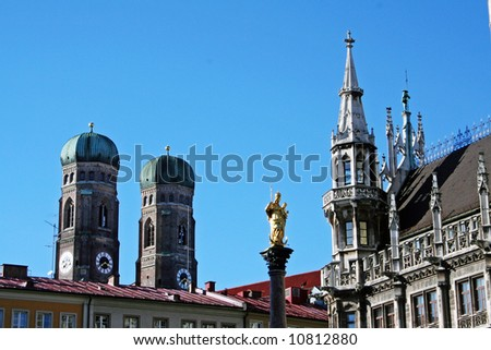 Munich. Detail of the town hall on Marienplatz withe statue of Virgin Mary. In the background, the mighty towers of church Frauenkirche. - stock photo
