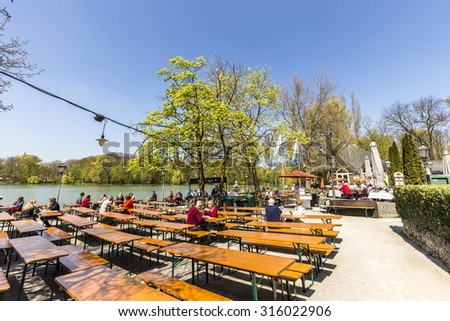 MUNICH, GERMANY - APR 20, 2015: people enjoy the beautiful weather at the Seehaus in Munich, Germany. This Beergarden is placed at the Kleinhesseloher lake in the English Garden. - stock photo
